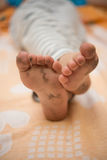 Boy lying with dirty feet Stock Images