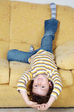Boy lying down on the sofa at home Stock Images