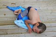 Boy lying down on a towel Royalty Free Stock Photos