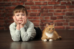 Boy lying on the floor with cat Royalty Free Stock Images