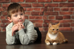 Boy lying on the floor with cat Royalty Free Stock Photos