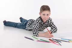 Boy lying on floor and drawing pictures. Stock Photos