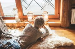 Boy lying on floor on sheepskin and looking in window in cozy home atmosphere. Peaceful moments of cozy home concept image royalty free stock photography