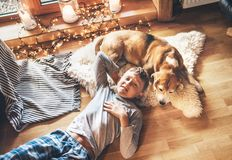 Boy lying on the floor and smiling near slipping his beagle dog on sheepskin in cozy home atmosphere. Peaceful moments of cozy. Home concept image stock photo
