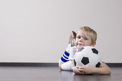 Boy Lying On Floor With Soccer Ball Stock Photography