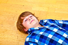 Boy lying at the floor Royalty Free Stock Photography