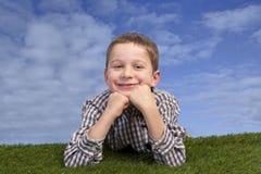 Boy lying on grass against blue sky Stock Image