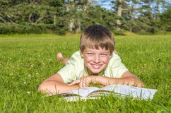 Boy lying on the grass with a book in the park Royalty Free Stock Photography