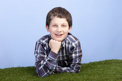 Boy lying on a grass field Stock Photos