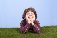 Boy lying on a grass field Royalty Free Stock Photo