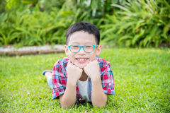 Boy lying on grass field and smiles Royalty Free Stock Photography
