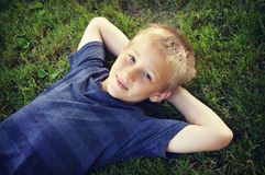 Boy Lying in Grass. A portrait of a young boy lying in the grass looking up into the camera stock photo
