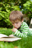 Boy lying on the grass reading a book Royalty Free Stock Photo