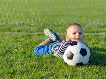 Boy lying on grass with soccer ball. Cute young boy with a frown on his face lying on grass with a soccer ball as he waits for someone to play with him Royalty Free Stock Image