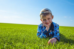 Boy lying on green grass Stock Photos
