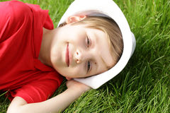 Boy is lying on green grass Stock Images