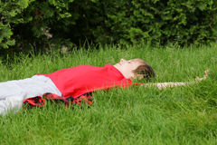 Boy is lying on green grass Stock Image