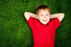 Boy lying on a green lawn Stock Image