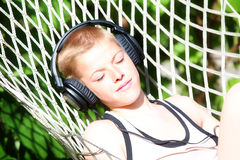 Boy lying in a hammock and listen to music on headphones. Summer Stock Image