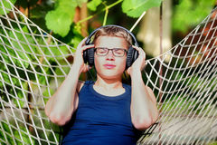 Boy lying in a hammock and listen to music on headphones. Summer Royalty Free Stock Images