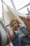 Boy (6-8) lying in hammock, mouth open, front view, close-up, portrait (blurred motion, tilt) Royalty Free Stock Photography