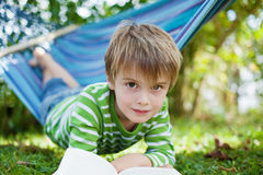 Boy lying in hammock and reading a book Stock Images
