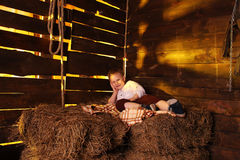 Boy lying on hay. Kid in a white shirt resting on hay Stock Photo