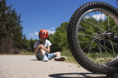 Boy is lying hurt after a bicycle accident Stock Photos