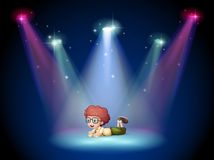 A boy lying in the middle of the stage with spotlights Stock Images