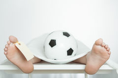 Boy lying on a mortuary slab with a soccer ball Stock Image