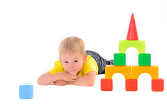 Boy lying near toy building of colored cubes Royalty Free Stock Images
