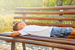 Boy lying on a park bench in dawn summer time. Royalty Free Stock Photos
