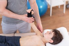 Boy lying on physiotherapy plinth. Image of boy lying on physiotherapy plinth doing exercises Stock Photos