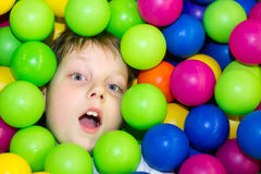 Boy lying in a pile of colored balls Stock Photography