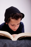 Boy lying on a pillow reading Royalty Free Stock Photography