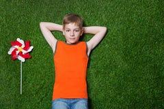Boy lying with pinwheel on green grass stock image