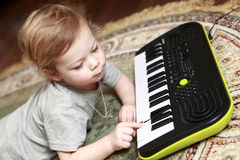 Boy lying and playing on synthesizer Stock Photos