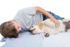 Boy lying with puppy on blanket Stock Photography