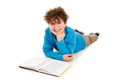 Boy lying and reading book Stock Image