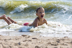 Boy lying on the sand in the sea Stock Images