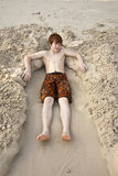 Boy  is lying in a sandy bed Royalty Free Stock Images