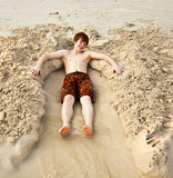 Boy  is lying in a sandy bed at the beauti ful beach Royalty Free Stock Photo