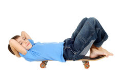 Boy lying on a skateboard Royalty Free Stock Image