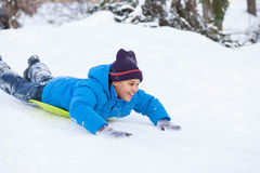 Boy lying on sledges and sliding down hill. Stock Photography
