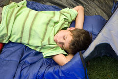 Boy (8-10) lying on sleeping bag in tent entrance, eyes closed, sleeping with hands behind head, side view Royalty Free Stock Photo