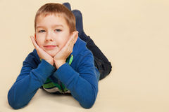 Boy lying, smiling and looking into camera. Royalty Free Stock Image