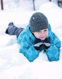 Boy lying in a snow Stock Photos
