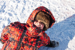 Boy lying in the snow Royalty Free Stock Photos