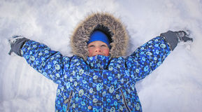 Boy lying in the snow, with his hands up. The boy is wearing a blue jacket and blue mittens Stock Photography