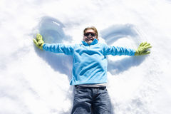 Boy (7-9) lying in snow making 'angel wings', smiling, overhead view Stock Photos